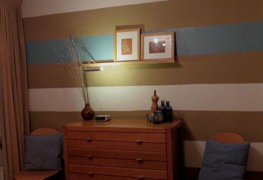 Streepwand in de slaapkamer. matte muurverf bruin en wit en staalblauw zijdeglans, over het bestaande behang heen.