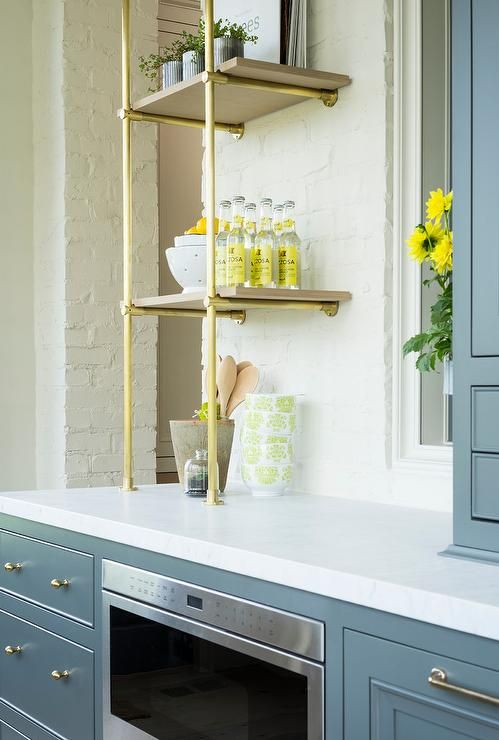 Gray butler pantry shelves fitted with brass knobs and and a stainless steel under counter microwave are topped with white quartz countertops holding brass and wood shelves against an exposed white brick wall.