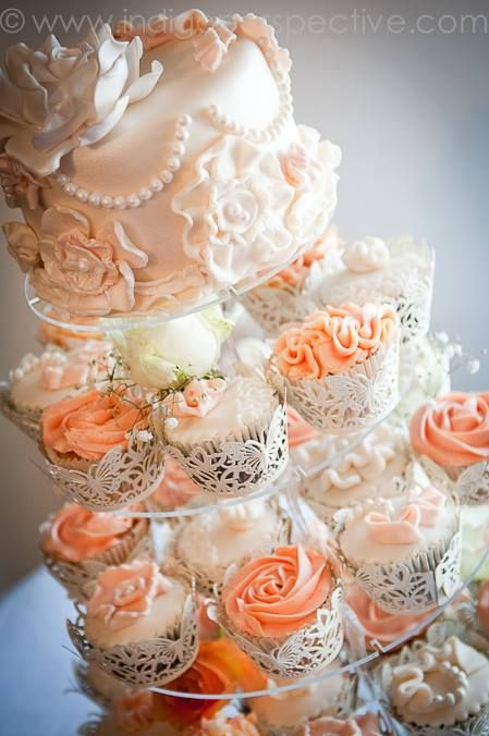 Tarta vintage hecha con cupcakes y frosting de color melocotón.