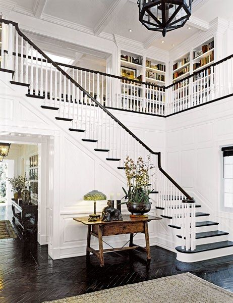 A traditional double-height entrance hall boasting dark wood floors | archdigest.com