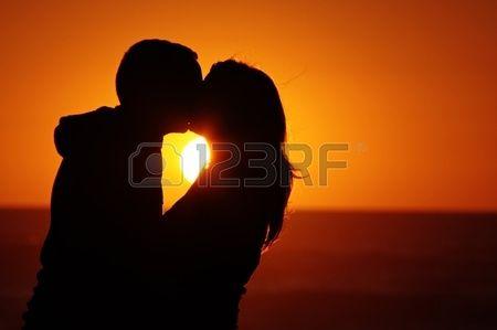 Una coppia sulla spiaggia con sfondo tramonto Archivio Fotografico