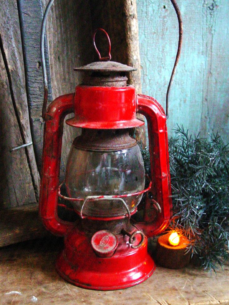 vintage red lantern tarted up for christmas. thats the key for decorating at the cabin i think...use the things that are always there, add some red or plaid, some greenery and twinkle lights! voila!