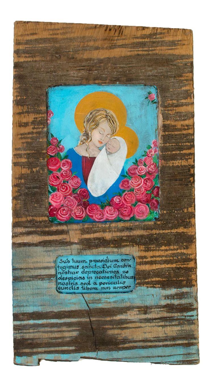 """Malować można na wszystkim, co nas inspiruje, ale stare drewno ma duszę. Deską wyszperałam u znajomego stolarza, który rozumie moja pasję i odkłada dla mnie co ciekawsze kawałki dębu czy buku.  Namalowałam Madonnę z Dzieciątkiem w otoczeniu róż i opatrzyłam napisem po łacinie """"Sub Tuum praesidium..."""", co znaczy """"Pod Twoją obronę..."""". Wymiary obrazu : 62 cm x 32 cm. Waga : 5kg."""
