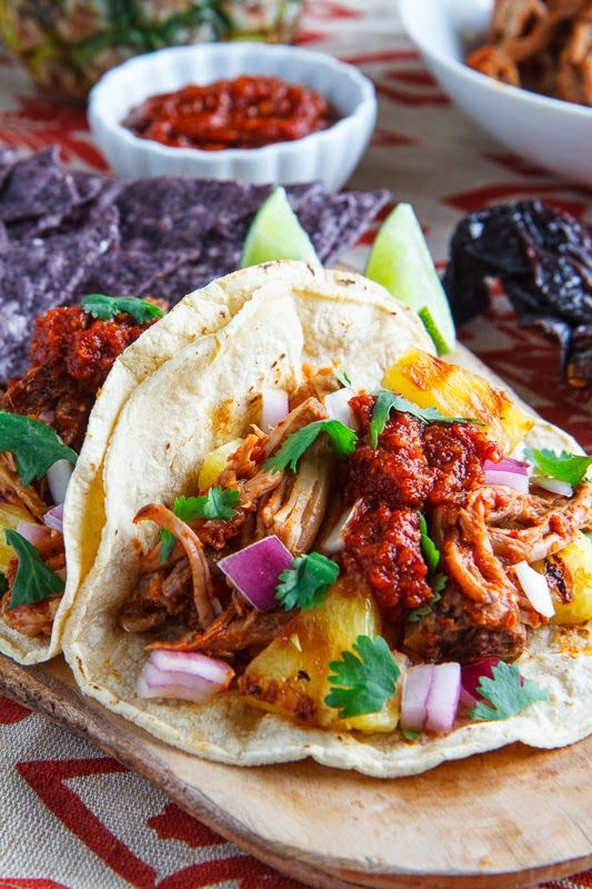 "Tacos al Pastor - "" Al pastor is a Mexican pork that is marinated in chilies and pineapple, layered and roasted on a vertical rotisserie similar to shawarma....great in tacos, burritos, quesadillas, enchiladas, etc."" (yummy dish for a those low carbers that include pineapple"