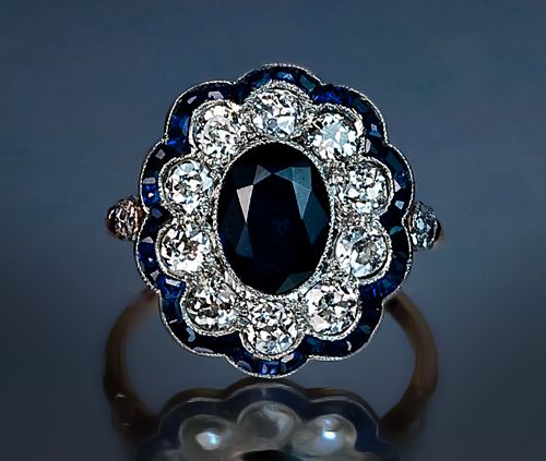 An Edwardian Era Sapphire and Diamond Engagement Ring circa 1910 This finely crafted fancy cluster ring features an oval sapphire center in a millegrain pl