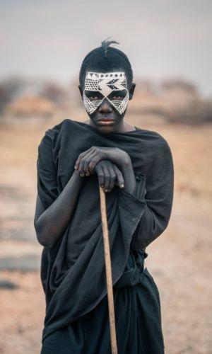 """O garoto da foto é conhecido como Nyangulo e faz parte da tribo Masai. A imagem faz parte do ensaio feito em outubro de 2015 pelo fotógrafo romeno Vlad Cioplea, durante expedição à Tanzânia. Cioplea conta que os garotos masai passam por um doloroso processo de crescimento. """"Eles são circuncidados e então têm que deixar suas casas por pelo menos três meses para aprender a sobreviver por conta própria no deserto. Eles devem vestir-se de preto e pintam seus rostos com branco"""", conta"""
