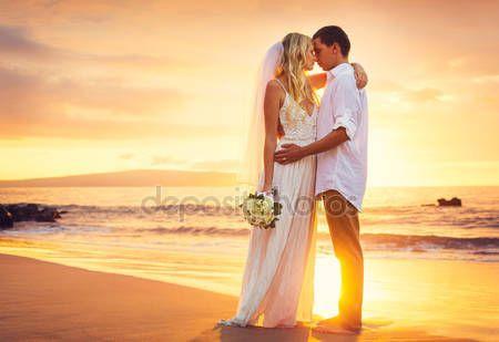 Menyasszony és a vőlegény, egy gyönyörű trópusi tengerparton naplementekor csók — Stock Fotó