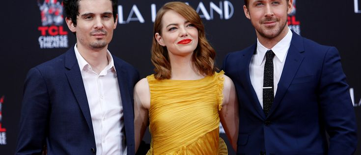 Director Damien Chazelle (L) poses with actors Emma Stone and Ryan Gosling after they placed their handprints, footprints and signatures in cement during a ceremony in the forecourt of the TCL Chinese theatre in Hollywood, California U.S., December 7, 2016.   REUTERS/Mario Anzuoni - RTSV5N3
