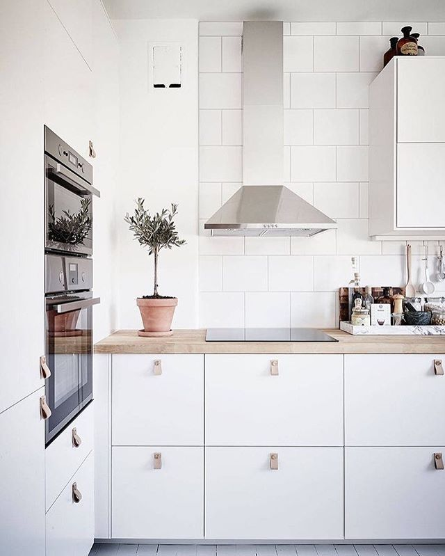 Gorgeous white kitchen via @stadshem I love the idea of these leather drawer pulls and of course the marble tray is a must for storing condiments and utensils