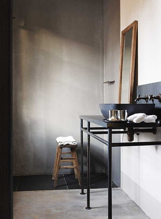 Love the simplicity.  Concrete walls with wooden mirror and stool accent.  Charcoal sink.