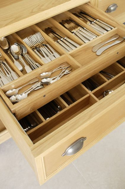 "The cutlery drawer is double layered, with secondary-use cutlery on the bottom layer and daily-use pieces on top.  ""The dots are magnets that lock the top drawer onto the front, so when the drawer is opened it doesn't slide back unless you want it to,"" -Transitional Kitchen by Artichoke"