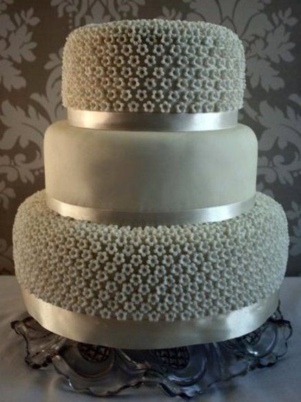 Three tier cake covered in over a thousand tiny blossoms