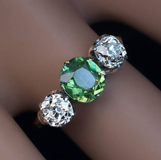 Antique Russian Demantoid Diamond Three Stone Ring, Circa 1900. This engagement ring features an excellent Russian demantoid from the Ural Mountains flanked by two bright white and sparkling antique cushion cut diamonds set in silver over gold.