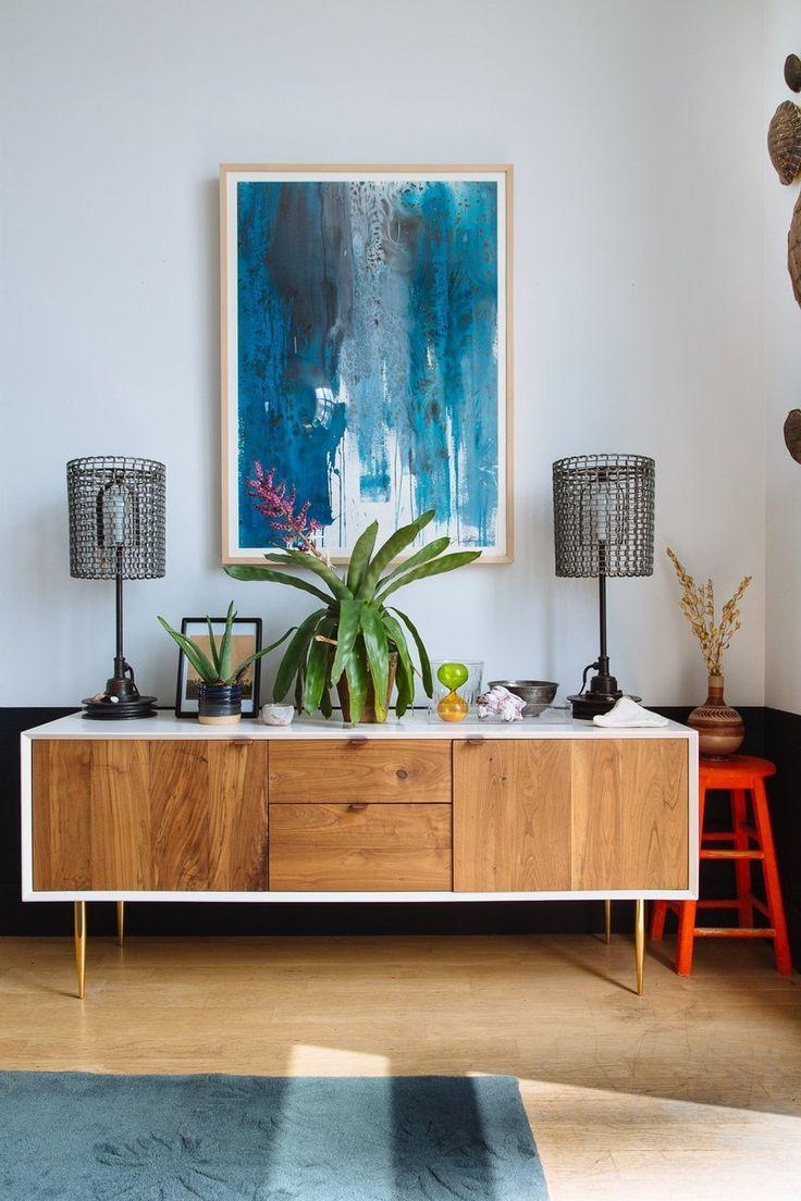 De combinatie van het blauwe schilderij met de houten kast met witte rand geeft een mooi kleurcontrast weer, door de plant in het midden, wordt er rust gecreëerd. | #MeijsWonen Moodboardactie | Irene Welten |