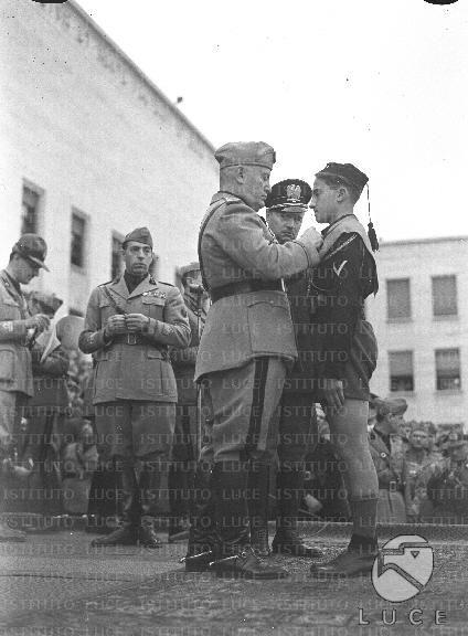 Mussolini consegna una medaglia alla memoria all'orfano di un caduto nel corso delle celebrazioni per il XVIII Annuale della Milizia Universitaria  ATTUALITA/A40-143/A00142002.JPG