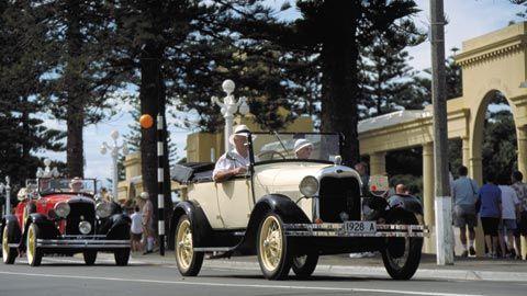 Classic cars driving down Marine Parade, Napier