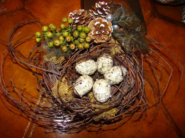 "I embellished this already wild nest with pine cones, berries, and sparkly holly leaves.  I added my ""song bird eggs""  made with paper mache eggs, torn song book pages, words, and sparkles.  By Valerie Young"