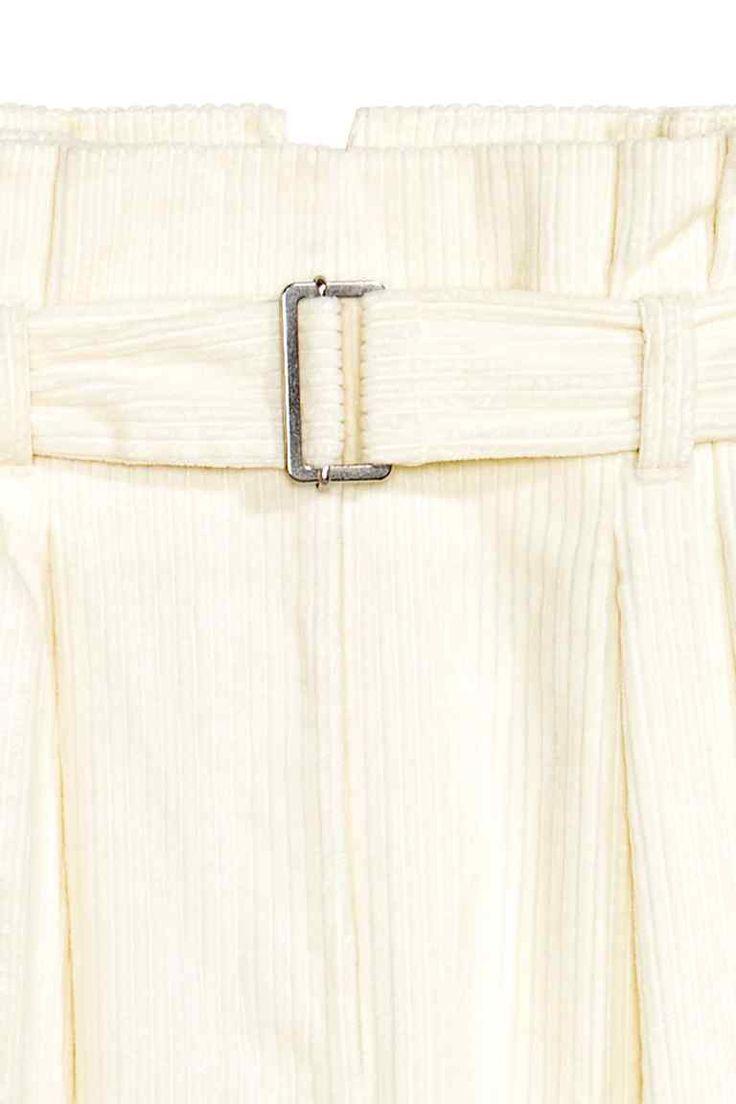 Широкие вельветовые брюки: STUDIO COLLECTION. Широкие брюки из плотного вельвета в широкую полоску. На брюках высокая талия, декоративные защипы и боковые карманы. Пояс с металлической пряжкой на талии. Застежка на молнию и пуговицу, а также на крючок.