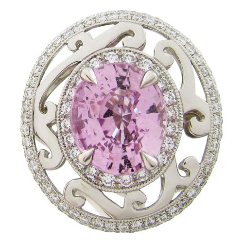 Whimsical and enchanting, this Suzanne ring is a statement and sure to be a conversation piece. The ring features an oval pink Sapphire which is framed by a double diamond halo and scroll work all around.  Oval Pink Sapphire, 3.63CT. Round Brilliant Diamonds 0.66TCW, VS-SI clarity, F/G colour. Platinum Ring. Ring Size 6.75. Style (R536).