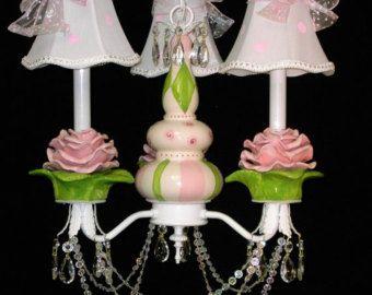 Teiera e lampadario di tazze di tè  Questa teiera tè e tazze e piattini lampadario presenta una teiera estrosa dipinti a mano, circondata da tre dipinti a mano tazze e piattini. Ogni tazza e piattino è dipinto in diversi colori e modelli di pois, boccioli di rosa, turbinii, ecc... con bella cristallo gocce appeso sotto ogni piattino! Le tonalità di seta a pois sono vendute come unopzione per $36 per il set di tre. Questo lampadario whimsical sarebbe un essere un favoloso accento per…