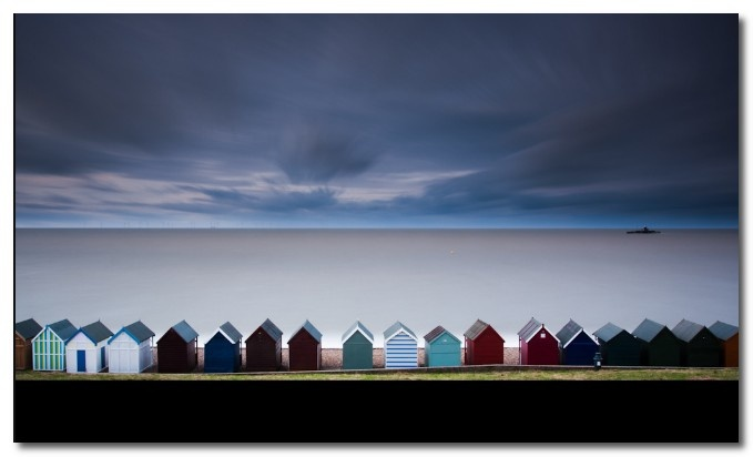 Photograph the beach huts along the beach in Herne Bay