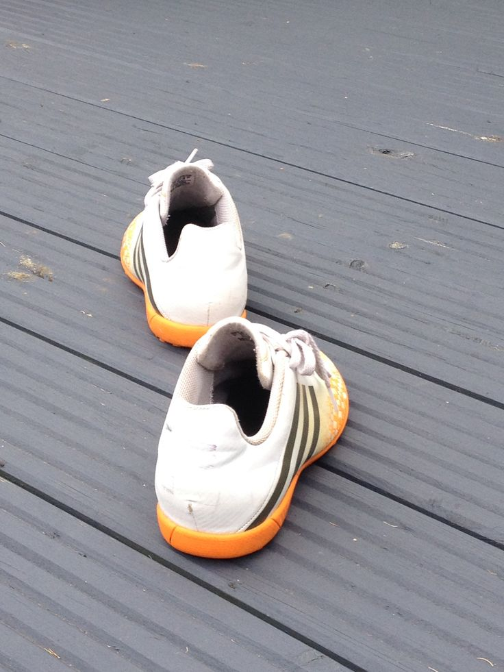 white and orange astro turf boots
