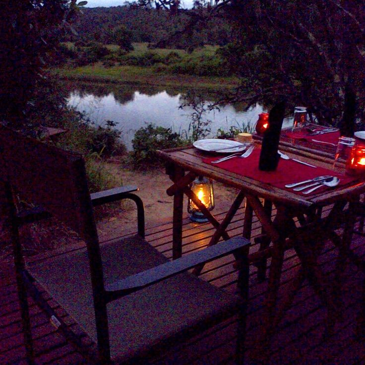 Private dinner setting on a deck overlooking the Kariega River at Sibuya Game Reserve. Kenton on Sea, Eastern Cape, South Africa www.sibuya.co.za