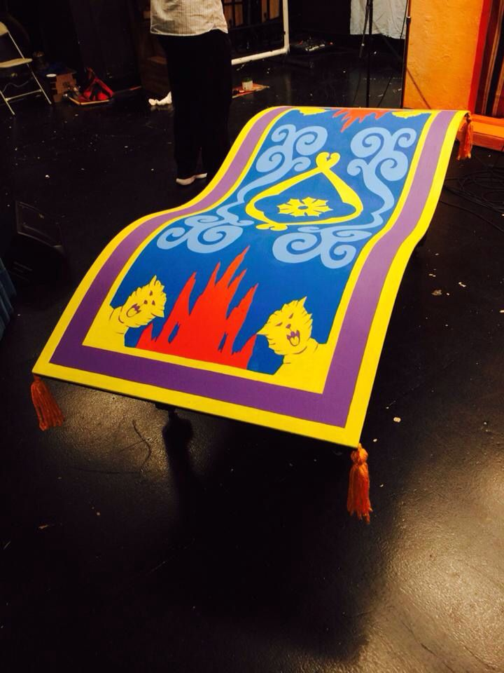 magic carpet (on wheels) for Aladdin; wood, masonite, painted, with tassels