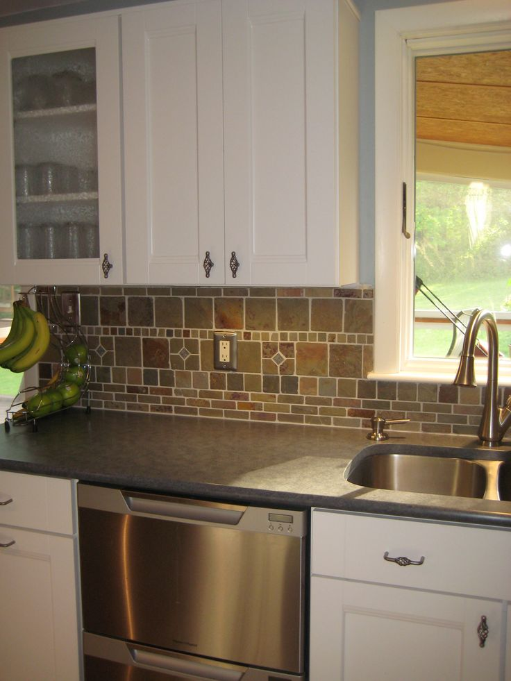 white cabinets dark countertops and slate backsplash
