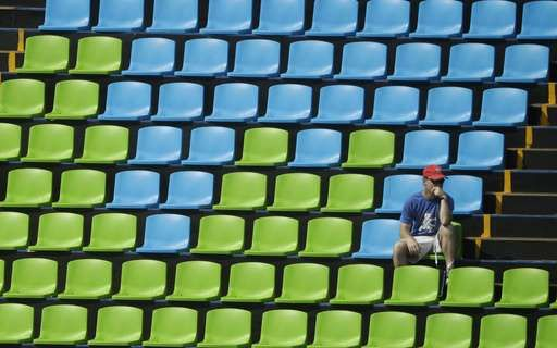 A fan sits surround by empty seats at the equestrian eventing dressage competition at the 2016 Summer Olympics in Rio de Janeiro, Brazil, Sunday, Aug. 7, 2016. (AP Photo/John Locher)