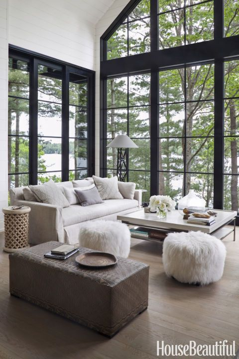 CANADIAN LAKE HOUSE: FLUFFY FOOT STOOLS – In the living room of an Ontario cottage, a 20-foot-high wall of windows provides sweeping vistas of Lake Joseph. Designer Anne Hepfer had the ottoman in the foreground custom made using vintage woven mats from Borneo. Click through for more summer houses.