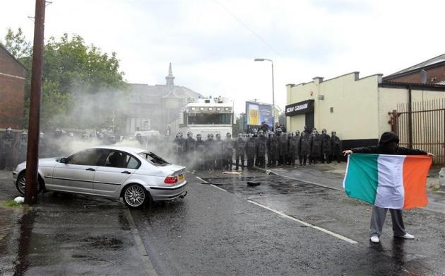 A nationalist youth displays the Irish National Flag beside a burnt-out car and riot police after trouble erupted in the Ardoyne area of North Belfast, Northern Ireland July 12, 2012. REUTERS-Cathal McNaughton