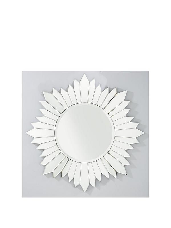 Michelle Keegan Faceted Sundial Wall Mirror – 91 cm diameter A stunning design from the exclusive range of homewares by Michelle Keegan, this gorgeous mirror gives your walls a spectacular focal point. The circular panel is surrounded by a frame made from a series of reflective faceted panels, creating a unique look that's reminiscent of traditional sundials. At 91 cm wide, this breathtaking beauty is perfect for a feature wall, and it helps to increase the perception of light and depth in…