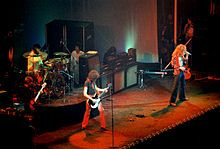 A colour photograph of the four members of Led Zeppelin performing onstage, with some other figures visible in the background