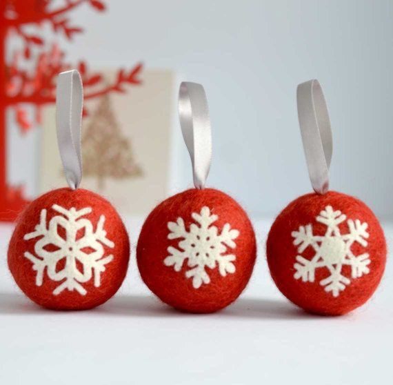 This set of three handmade Scandinavian inspired felted Christmas balls are a great addition to your Christmas tree adding to the cosiness and happiness in your home during the festive season. The red Christmas balls are felted using hand-died Norwegian wool, filled with lambswool, and fitted with a silver coloured satin ribbon. Each of them is decorated with a different snowflake made of white wool felt.  Each Christmas ball is about 6cm in diameter and weighs about 16 grams.