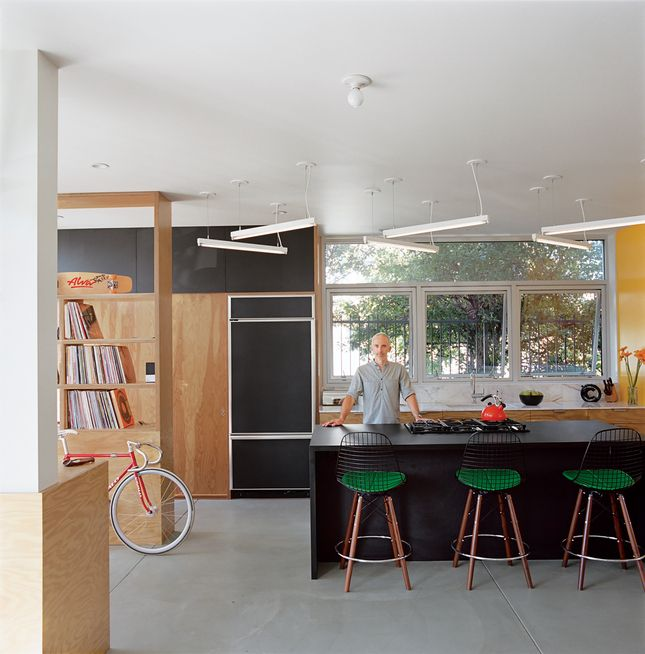 """Riffing on the Los Angeles phenomenon of people """"murdering out"""" their cars—that is, removing all the trim and blacking everything out—architect Barbara Bestor and craftsman Eric Lamers covered most surfaces in this Los Angeles kitchen with matte black laminate, including the fridge and the overhead cabinets."""