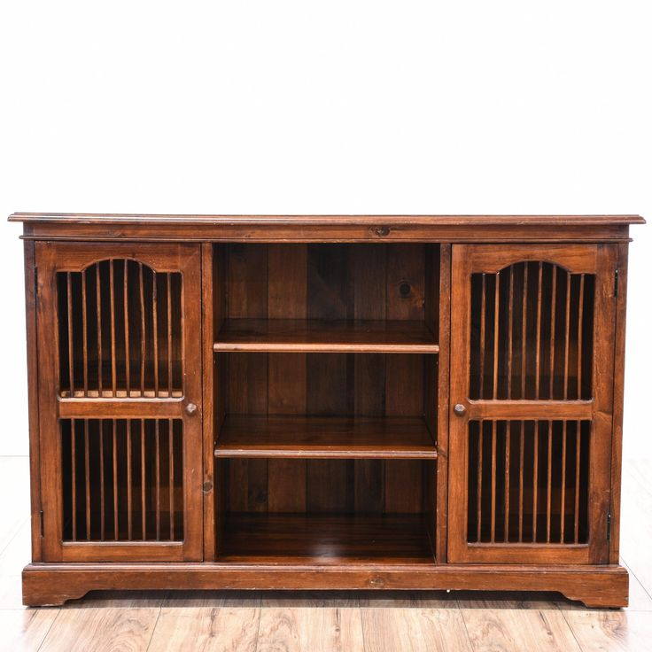 This entryway table is featured in a solid wood with a mahogany stain. This traditional style media cabinet has 2 side cabinets, 3 rows of shelving, and carved trim. Perfect for extra storage! #americantraditional #storage #mediacenter #sandiegovintage #vintagefurniture