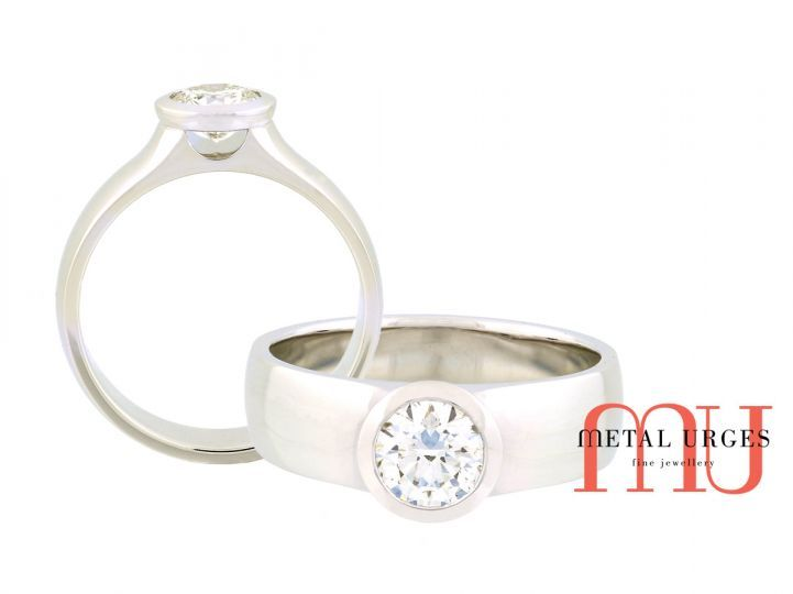 1ct round brilliant cut white diamond ring. The GIA certified diamond is centrally bezel set in 18ct white gold leaving U shaped openings below the setting. The solid white gold band feature raised swept up shoulders. Handmade in the Metal Urges workshop, Tasmania.