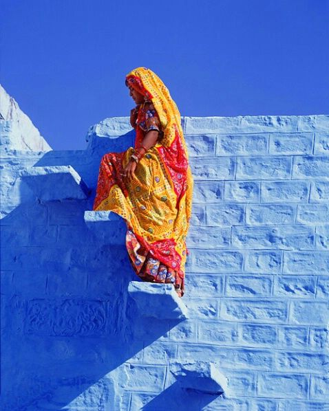 A particularly striking shot of a woman draped in Indian yellows and analogous tones, set against the contrasting right swathes of sky blue. This creates an otherworldly atmosphere within the images that makes the woman look as if she's about to walk in to infinity.