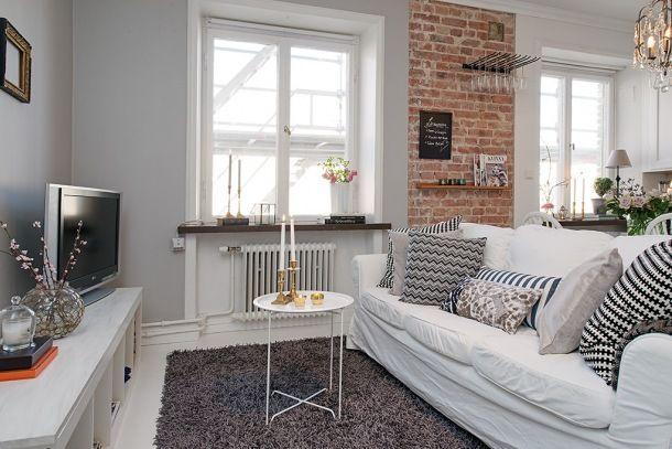 biały salon skandynawski ze ścianą z czerwonej cegły