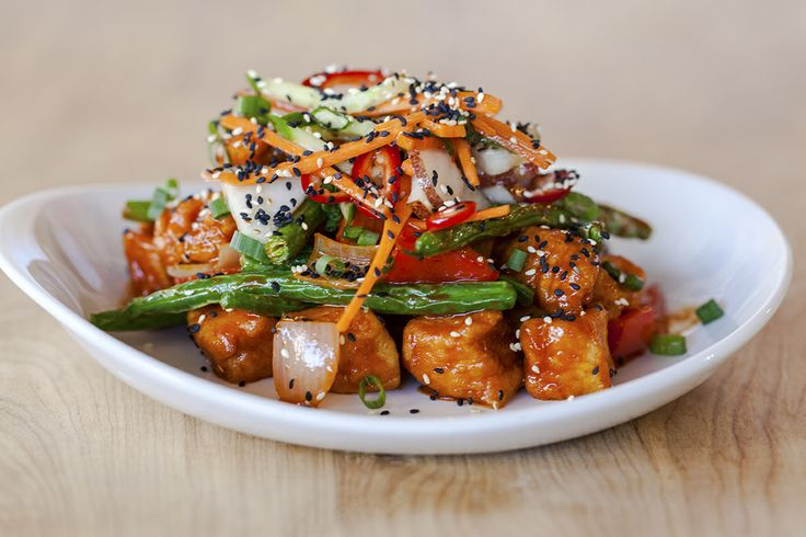"""KOREAN BBQ CHICKEN STIR-FRY Tender chicken breast stir-fried with fresh red peppers, onions and green beans in a sweet & spicy red chili sauce, topped with a cool, refreshing kimchi slaw WINE PAIRING Penfolds """"Thomas Hyland"""" Shiraz"""