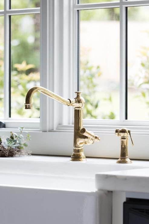 An antique brass vintage faucet is paired with a farmhouse sink and fixed in front of a window to a white marble countertop.