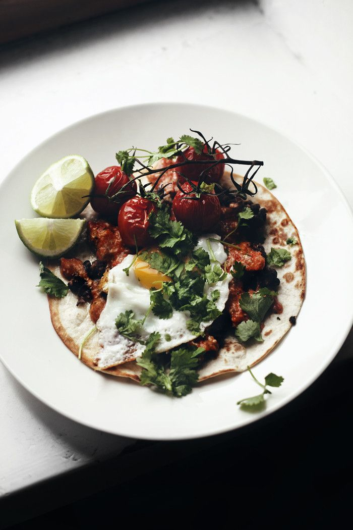 Breakfast tostada with black beans, tomatoes, cheddar and egg.