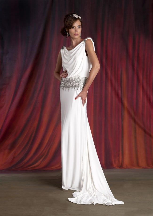 Mary by Eliza Jane Howell is a Grecian inspired column gown with draped cowl neckline, dropped waist with silver embellishment, matching embellishm...