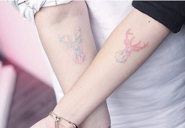 Matching polygonal deer head tattoos.