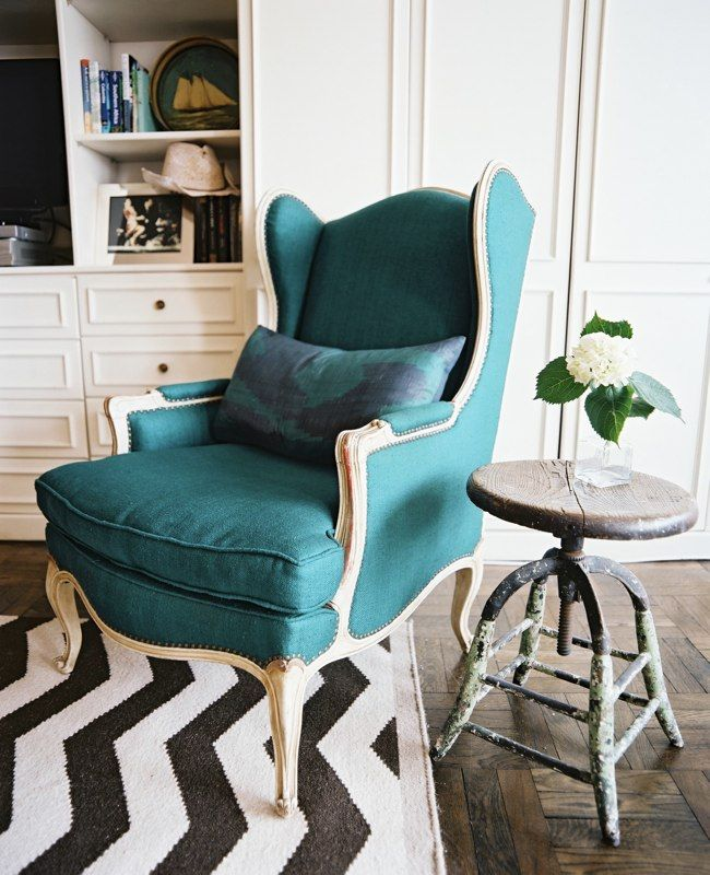 My fave color on the chair, a rustic old stool for side table and a fresh chevron rug all make this a super hip room!