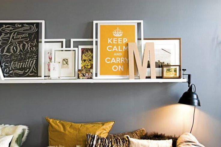På en bildelist i stuen har eieren samlet posters, bilder og bokstaver. Plakaten i svart til venstre er fra seblester.co.uk. De andre bildene er blant annet fra Arild Ytri og Therese Nordtvedt - i tillegg til at noe er studentarbeider. Bokstaven i tre er fra Kvist.