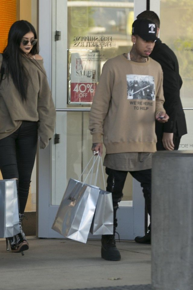 Tyga wearing Adidas Yeezy Season 1 950 Boots, Amiri MX2 Jeans, Last Kings Last Kings Records Logo Cap, Fear of God We're Here to Help Crewneck in Camel