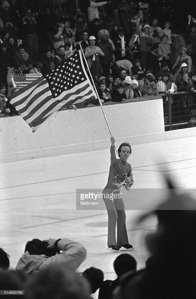 American figure skater Scott Hamilton carries an American flag as he skates on the ice in celebration of his victory in the men's figure skating competition at the 1984 Winter Olympics in Sarajevo, Yugoslavia.