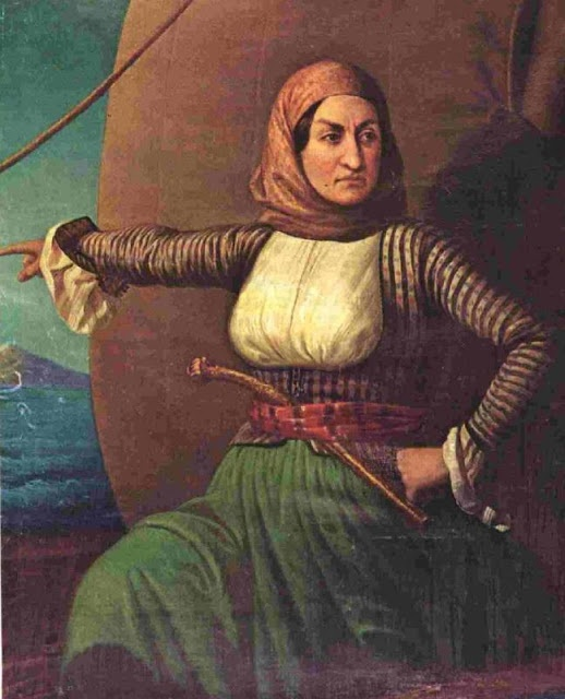 """With her little fleet of warships, Laskarina Bouboulina sometimes called a """"pirate queen."""" The only woman member of revolutionary organization that overthrew the Turks' Ottoman Empire, she raised the rebel flag on March 13, 1821, to signal the revolt that freed the Greeks for the first time in seven centuries. Attacking the impregnable fort at Nafplion, through a rain of bullets, her solders fell back at one point only to hear her shout, """"Are you women, then, and not men? Forward!"""""""